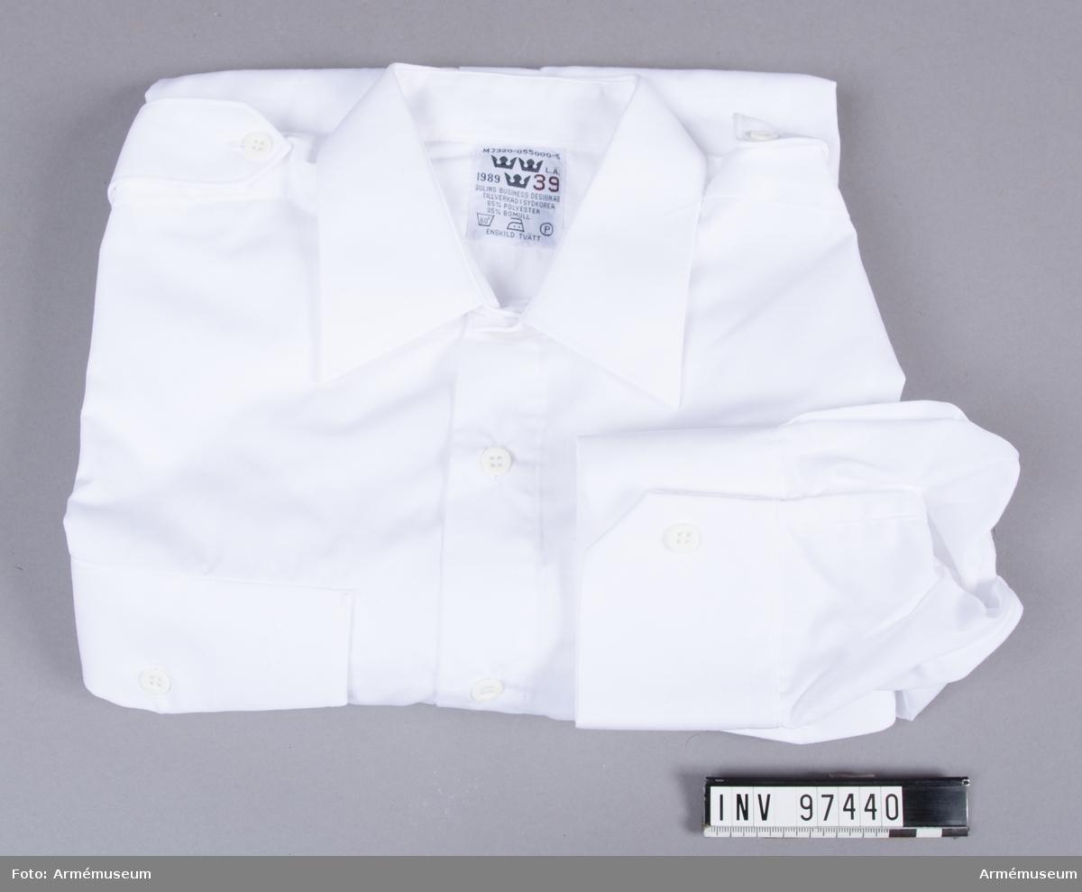 Vit skjorta i polyester och bomull, tillverkad i Sydkorea 1989. Med axelklaffar där axelhylsor kan fästas.