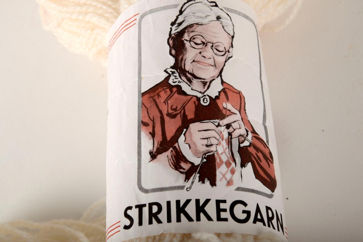 Eldre kvinne iført kjole og briller som strikker.