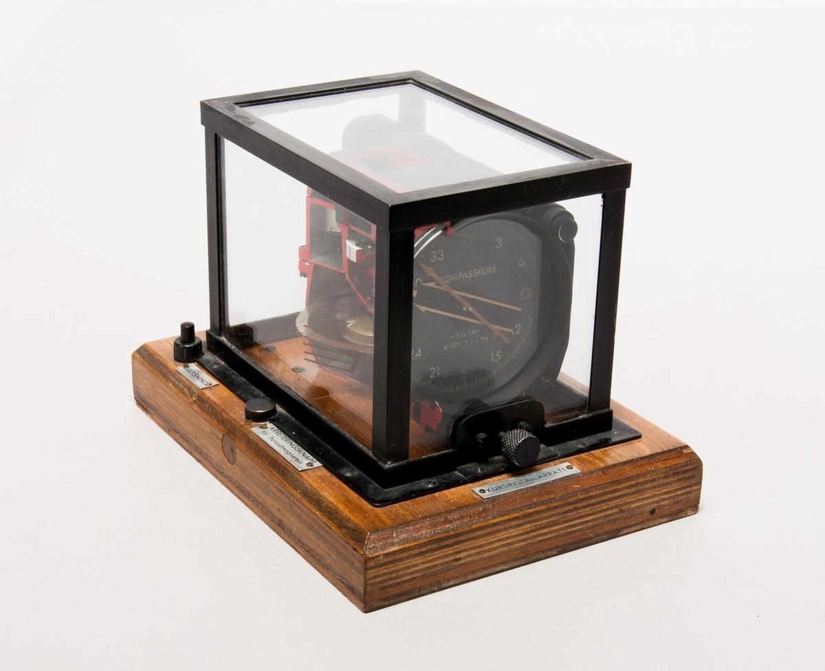 """Avskuren flygkompass i monter gjord av metall, glas och trä. Har skyltar med orden """"Kursinställarratt, Arreteringsknapp för huvudmagneten, Belysning"""" på sig. Kompassen går upp till 360 grader. Har en knapp vid """"Belysning"""" skylten. Har texten """"Kompasskurs, Silva"""" i kapseln av kompassen."""