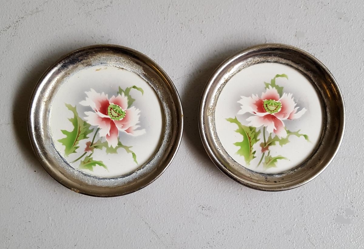 2 små sirkelrunde kuverbrikker/glasunderlag med stilisert blomstermotiv.