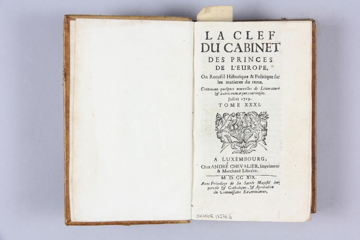 """Bok, helfranskt band """"La clef du cabinet des princes de  l´Europe"""", del 31, tryckt i Luxemburg 1719. Skinnband med blindpressad och guldornerad rygg i fem upphöjda bind, blindpressat titelfält, övriga fält närmast utplånade, påklistrad pappersetikett med samlingsnummer. Med stänkt snitt."""