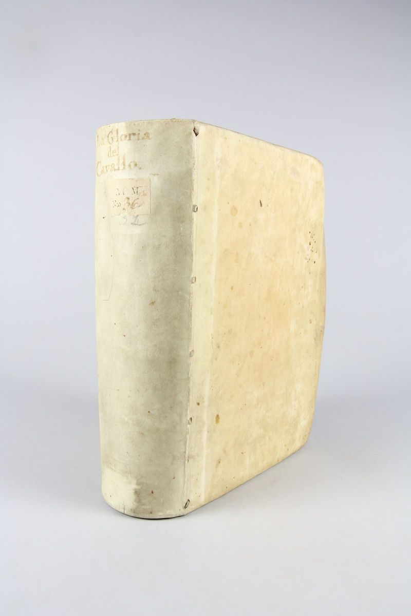 """Bok. pergamentband, """"La gloria del cavallo"""" tryckt 1608 i Venedig. Band av pergament, rött snitt. På ryggen bokens titel samt samlingsnummer. Anteckning om förvärv."""