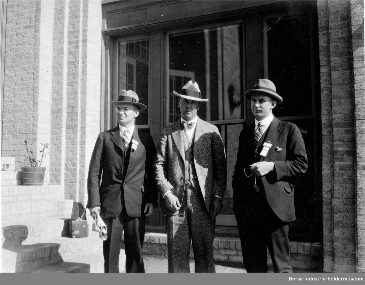 Tre menn foran lys mursteinsbygning.