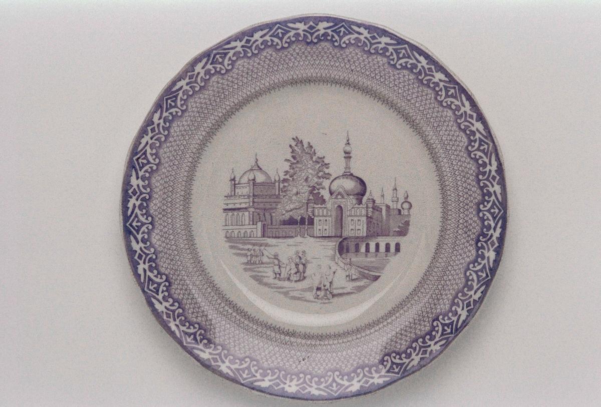 """A-D ) Flat tallrik av flintgods med vågigt brätte. Tryckt violett dekor mot vit botten, motiv med landskap och byggnader i orientalisk stil. Stämplad """" Gustavsberg / Stambul """". Tillverkad 1885-1905 med Arvid Ekberg som formgivare vid Gustavsberg. E-H ) Djup tallrik, i övrigt som ovan."""
