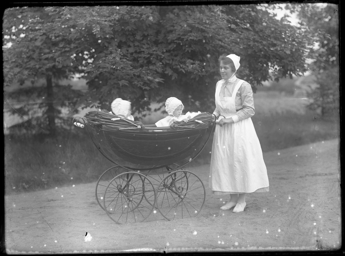 En sköterska kör en barnvagn med barnen Tollstadius på en gräsmatta. Troligen Ester och Birgit Tollstadius.