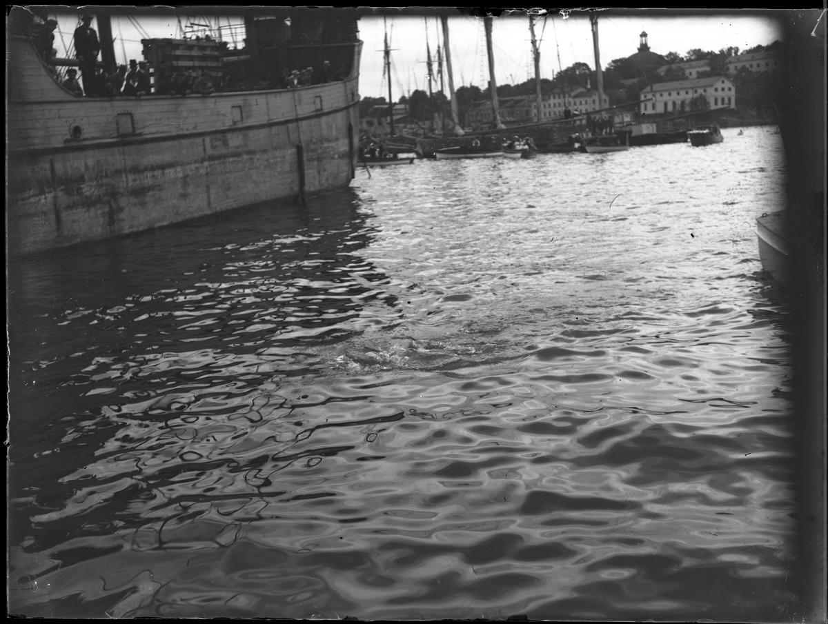 Bild tagen från Skeppsbrokajen över vattnet mot Skeppsholmen och Skeppsholmskyrkan. Ett antal skepp syns. Bilden togs under fotografen Harald Olssons excercistid.