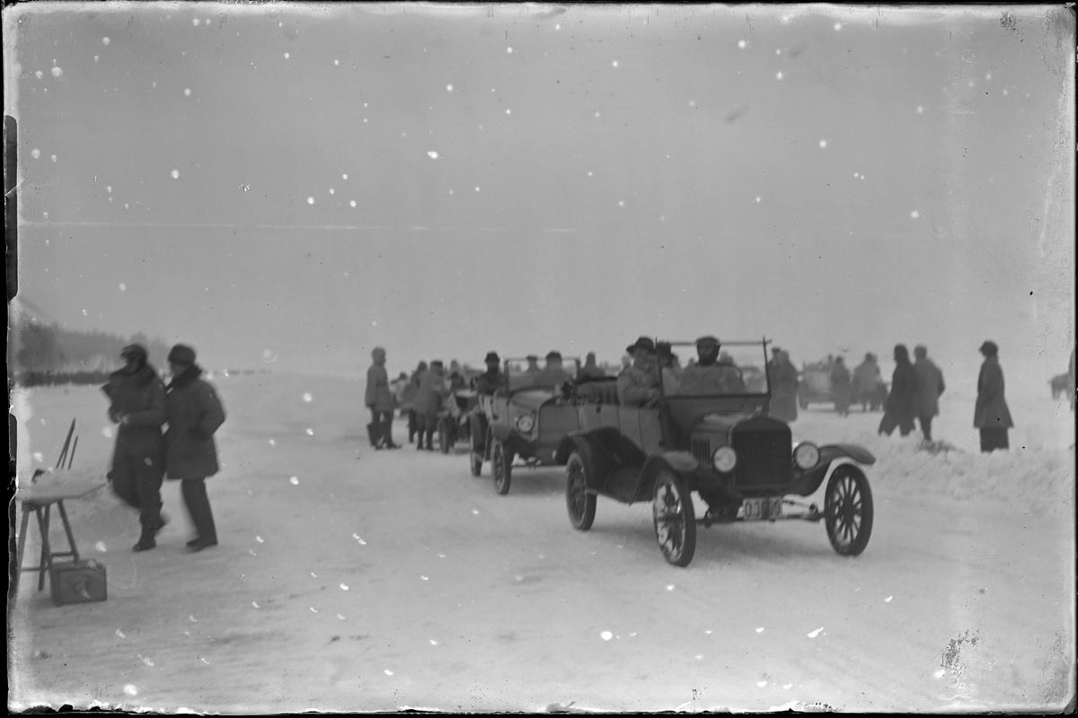 Bilar och åskådare ute på isen på Mjörn i samband med motortävling.