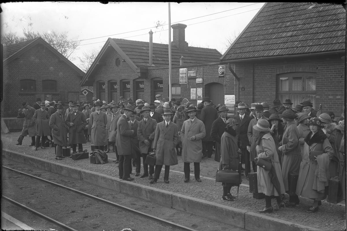 Tågresenärer på perrongen på Hörby station. I fotografens egna anteckningar står: Danmarksresan, Hörby station