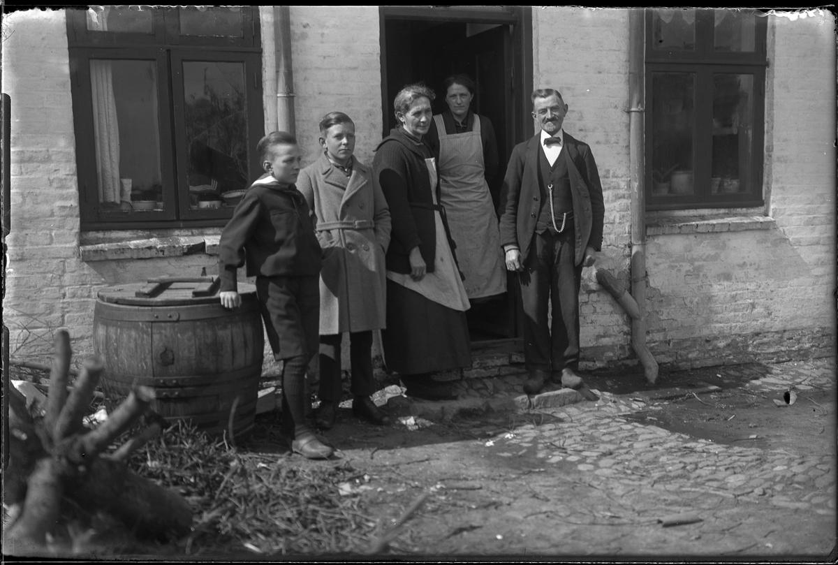 Två pojkar, två kvinnor och en man står i dörren till en vitkalkad tegelbyggnad. I fotografens egna anteckningar står: Danmarksresan, Petersén, Hjörring
