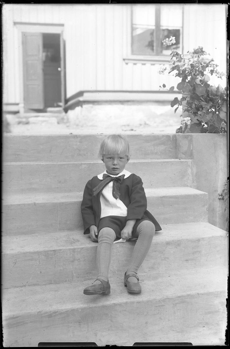 Porträtt av Arne Johansson som sitter på en stentrapp framför en träbyggnad. Han har mörka kortbyxor och jacka, vit skjorta och rosett i halsen.