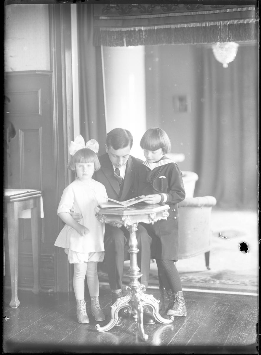 """En kostymklädd ung man sitter på en stol och bredvid honom står en pojke i sjömanskläder och en flicka i ljus klänning och rosett i håret. Tillsammans tittar de i en bok. I fotografens egna katalog står det """"Barnen Norinder""""."""
