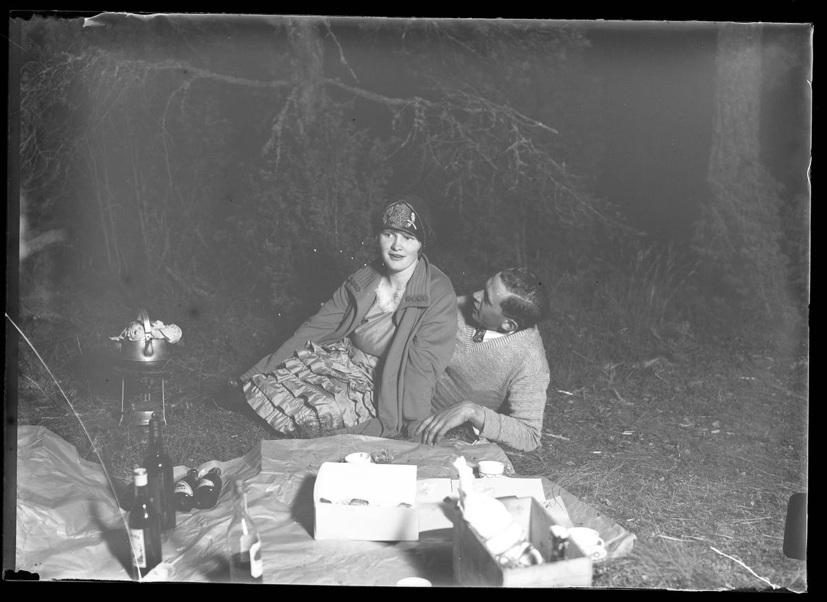 Hugo och Astrid har picknick på Risön. Framför dem står vita lådor, öl- och vinflaskor samt en kaffepanna på ett gasolkök.