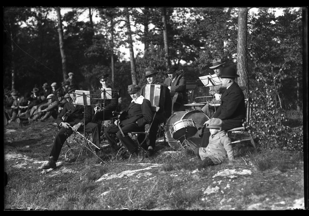 Ett antal musiker sitter på fällstolar i parken. I bakgrunden sitter män i olika åldrar i gräset.