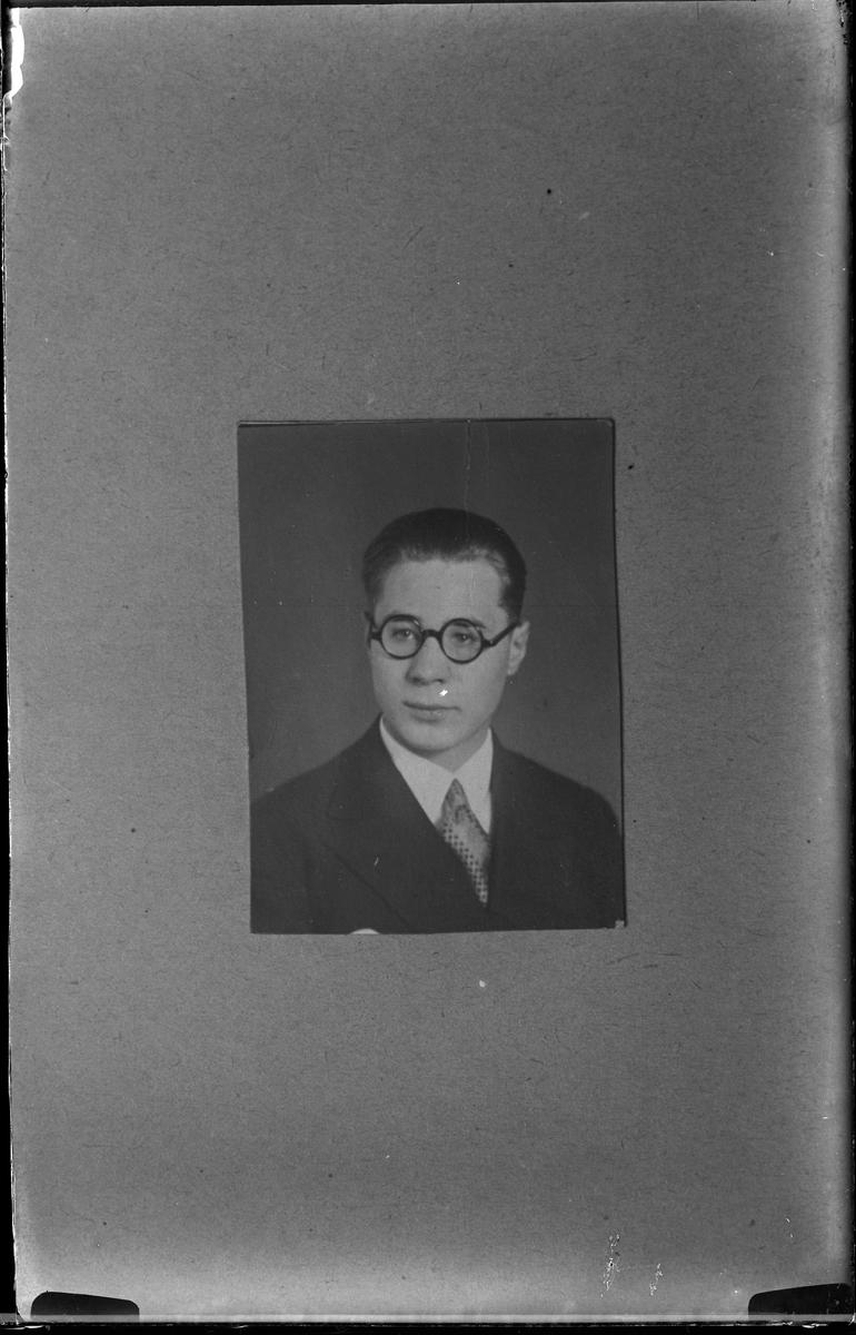 """Reprofotografi av en porträttbild på en man i kostym och runda glasögon. I fotografens egna anteckningar står det """"Repp. för fr. Vogel""""."""
