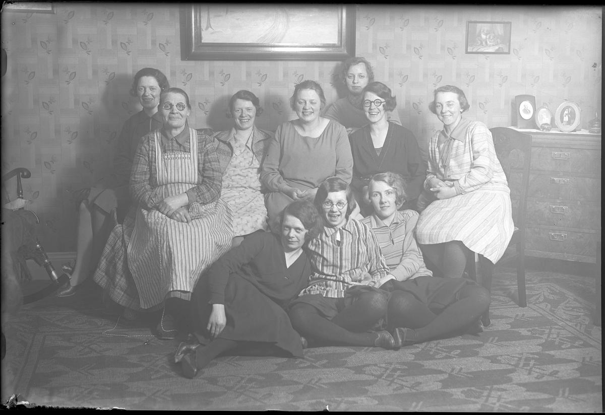 """Gruppbild på tio kvinnor som sitter uppradade i ett finrum. I fotografens egna anteckningar står det """"Dahlgrens symöte"""". På bilden syns Amanda Dahlgren (den äldre kvinnan i randigt förkläde) och på hennes vänstra sida sitter dottern Agnes och till höger möjligen dottern Thea. Dotter Ruth, klädd i svart, sitter på golvet nedanför sin mor, bredvid henne sitter Amandas barnbarn Britten och längst till höger syns Greta Dahlgren, gift med Amandas son Harald. Kvinnan i svart klänning och glasögon är Martha Liljedahl."""