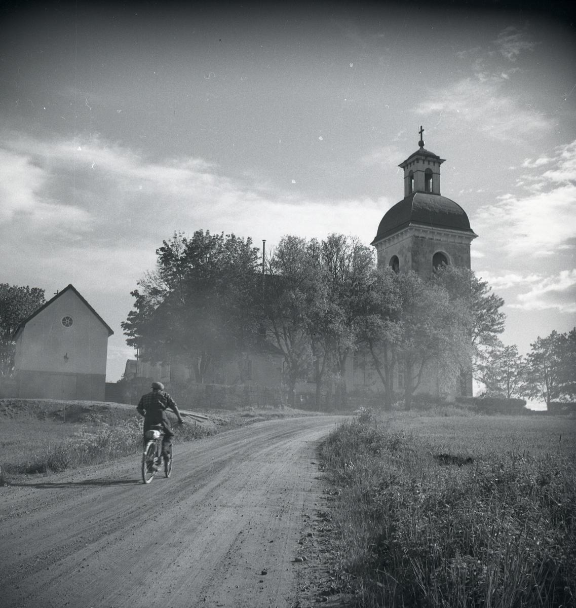 En man kämpar upp för en backe på sin cykel vid Jättendals kyrka.