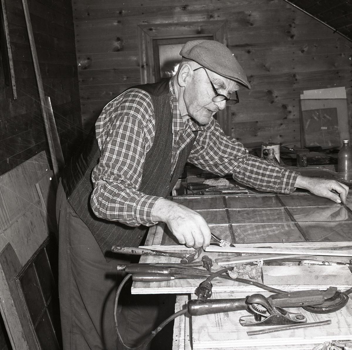 En man arbetar koncentrerat vid en bänk, 1968.