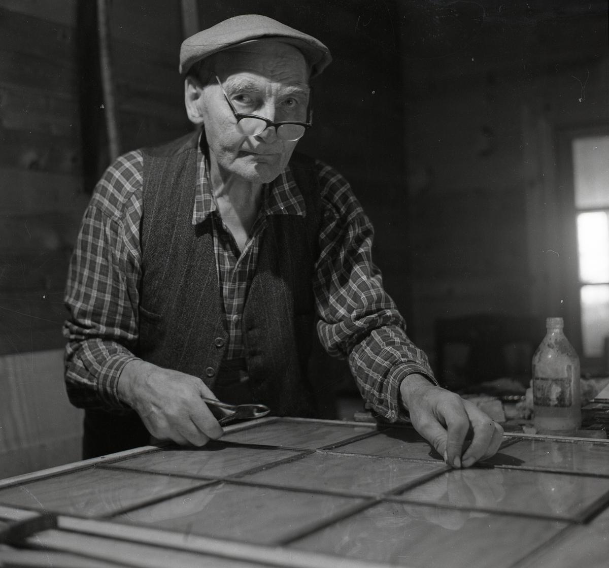 En man i keps och glasögon arbetar vid en bänk, 1968.