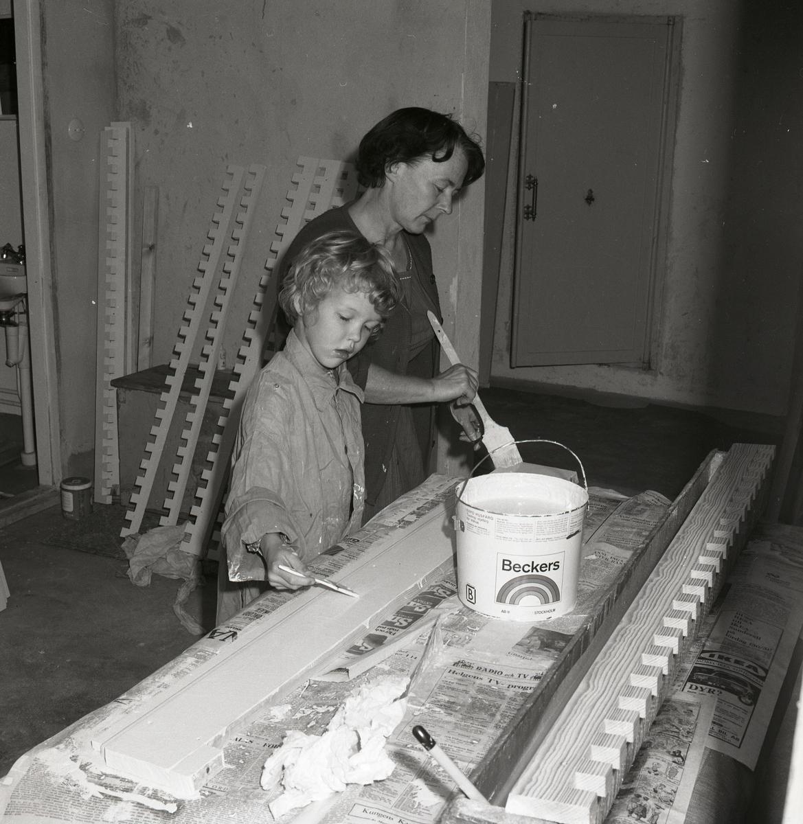 En kvinna och ett barn målar lister och överstycken, 1968.