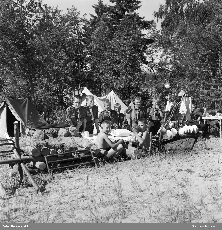I juli 1959 anordnade Svenska Scoutförbundet sitt stora internationella läger på Rödön utanför Alnö. På första bilden ses lägerledaren Tage Allegård anlända med en grupp pojkscouter för några intensiva veckor på ön. Lägret hade förberetts under ett helt år och dagarna innan hade 70 pojkscouter och ledare hjälpts åt att bygga upp de olika lägerbyarna, som fick namn efter olika fyrar.  SCA hade upplåtit en pråm som låg för ankar i hamnen fylld med de matvaror som krävdes för att mätta de cirka 800 deltagarna.