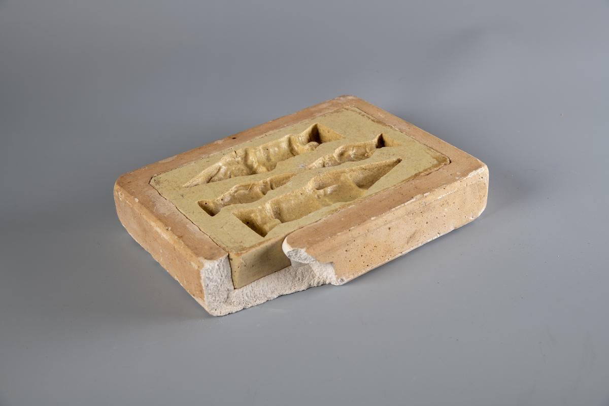 Rektangulær gipsform med avrundete hjørner. Formmotivet er to nisser, en stor og en liten.