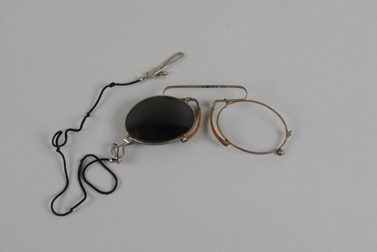 Lorgnett med mørke ovale glass. Lorgnetten har fjærbøyle forsynt med celluloïdforing på nesebøylene. Festesnor av svart silke. Det ene glasset mangler.