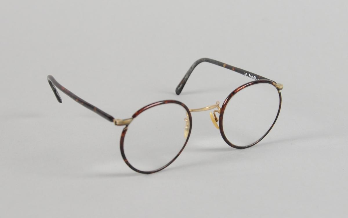 Runde briller med mørkebrun innfatning og nesebøyle av metall.