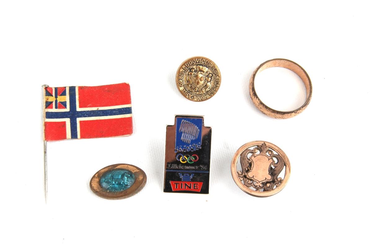 """En nål med papirflagg med unionsmerket (""""sildesalaten""""), samt fire ulike jakkenåler og  én ring."""
