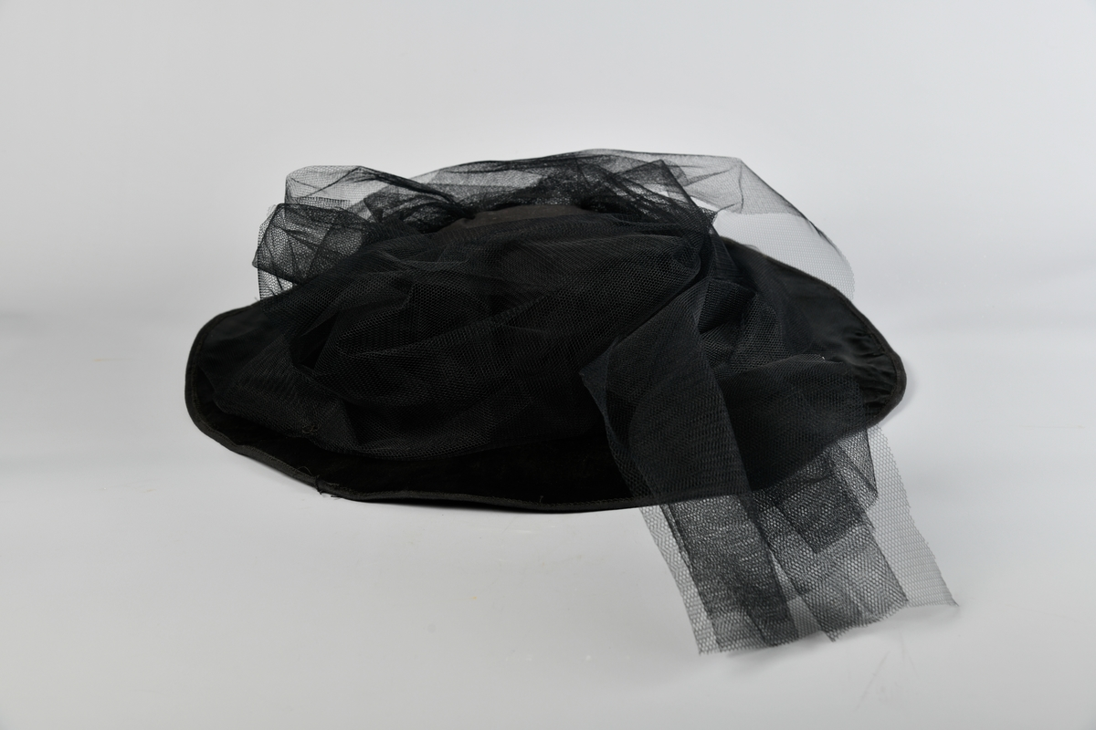 Bredbremmet hatt med rundt pull. Dekorert med sort tyll som er sydd fast rundt pullen. Pullen er foret med grønn filt. Inni pullen er det festet en tynn bommulslapp med påskrift: Wenche Føre på den ene siden, og bare Torhild på den andre. Usikkert når og hvorfor disse navnene er festet til hatten.