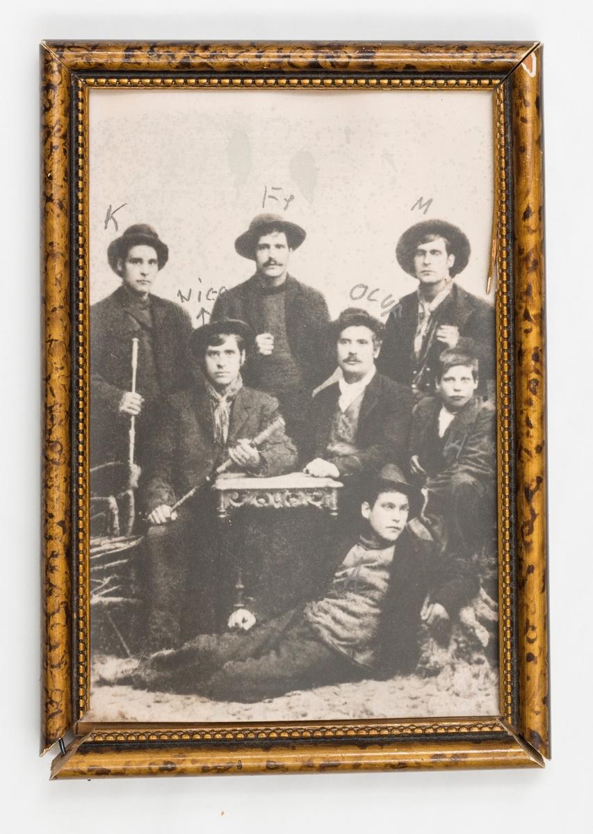 Fotografi i treramme. Det er avbildet 7 menn samlet rundt et bord. Det er satt bokstaver over noen av personene. Sort/hvitt bilde. Rammen er malt/lakket. Den har en bord innert mot bilde.