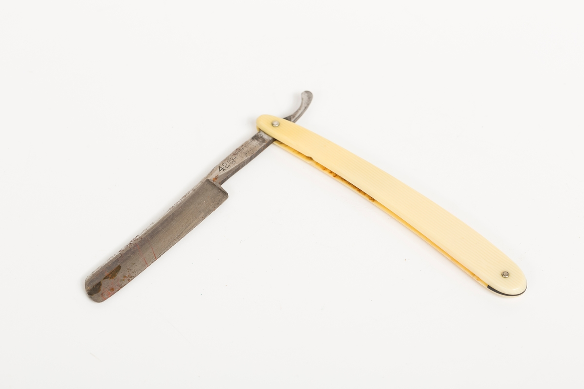 Barberkniv i stål med skaft i gulhvit plast.