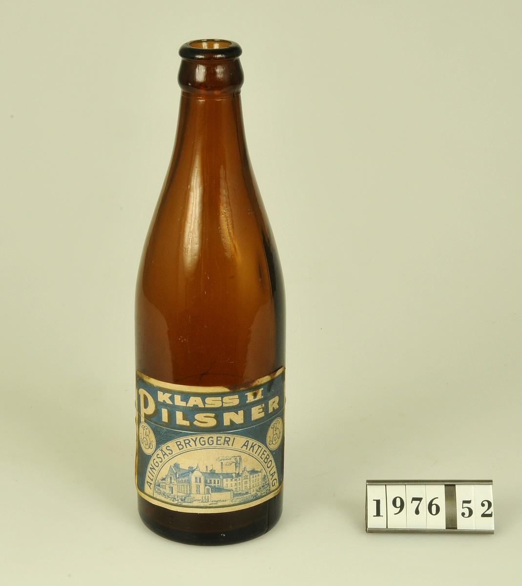 Pilsnerflaska av brunt glas med etikett.  Etikettens text: Klass 11 PILSNER ALINGSÅS BRYGGERI AKTIEBOLAG. Etikettens storlek: 9 x 6 cm. Vit text mot blå botten.