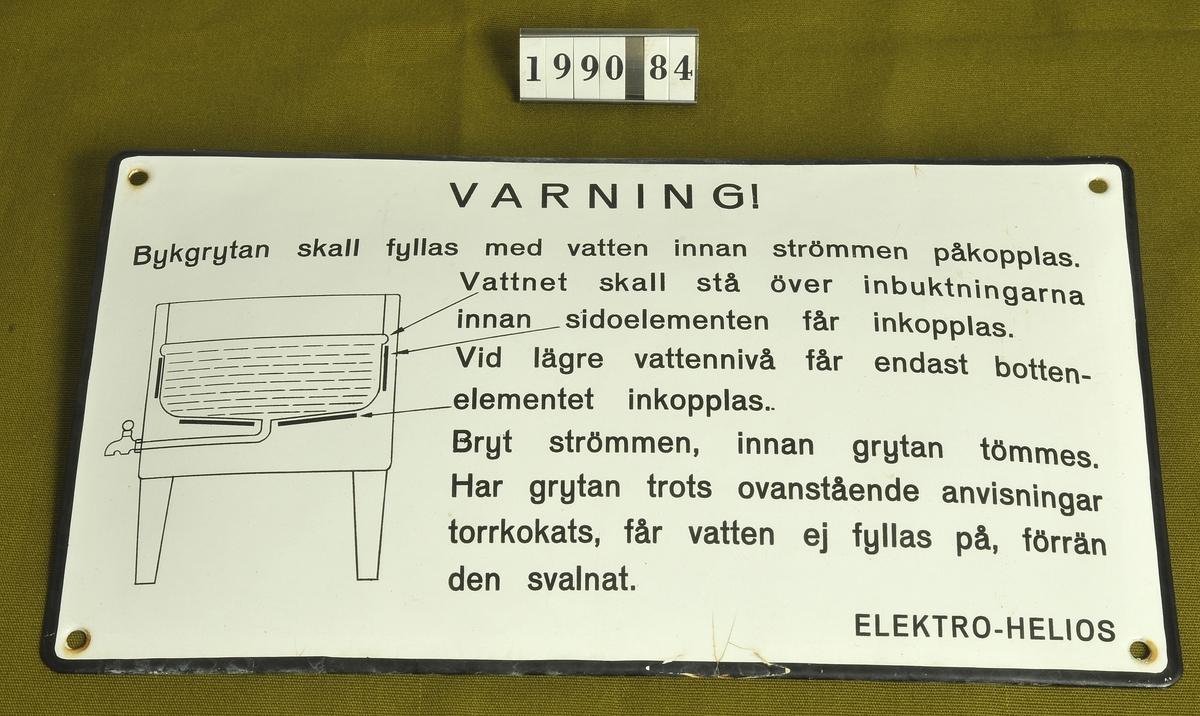 Svart text mot vit botten.Varningstext för tvättgryta. Elektro-Helios. Skruvas fast i väggen.  Tillvaratagen av museets personal i tvättstuga, Stockslycke, Alingsås.