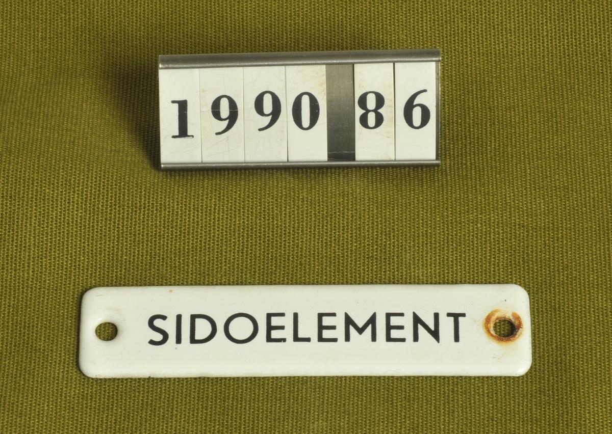 """Svart text mot vit botten: """"Sidoelement."""" Skruvas fast i väggen.  Tillvaratagen av museets personal i tvättstuga, Stockslycke, Alingsås."""