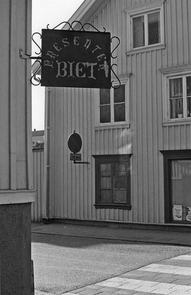 Butiksskylt i för present och hemslöjdaffären Biet. Kvarteret Hästskon 3 i hörnet av Nygatan och Drottninggatan.