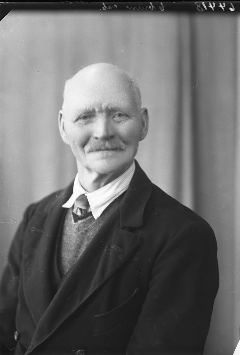 Portrett. Eldre mann med lite hår og bart i mørk dressjakke, strikket vest og slips. Bestilt av Hr. Odin Pedersen. Solbakken. Nordre Skaare.