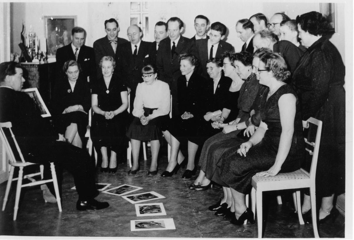 22 personer i halvcirkel framför en man som sitter på en stol. Framför sig, på golvet, ligger 5 bilder.  Folket-i-Bild ombud, Filip Wingqvist, distriktsombudsman för FiB. Håkan Johansson (stående nr 5 från vänster) var centralombud.
