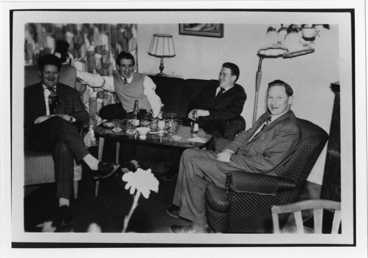 Fyra män på en födelsedagsfest sitter i soffa och fåtölj med flaskor och glas på ett soffbord.  Längst till höger sitter metallarbetare Folke Jansson.