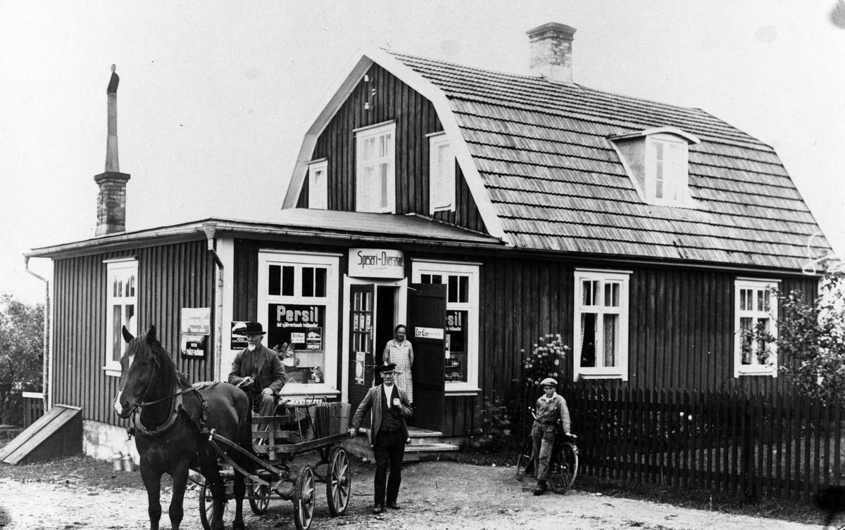 """En tvåplansvilla med tillbyggd affärsdel, Gråbo Speceriaffär. Ovanför affärsingången ses en skylt med texten """"Speseri-Diversehandel"""" och i dörröppningen står en kvinna i rutigt förkläde. Utanför affären ser vi en man med häst och vagn, en annan man som lutar sig mot hästvagnen samt en pojke som lutar sig mot en cykel."""
