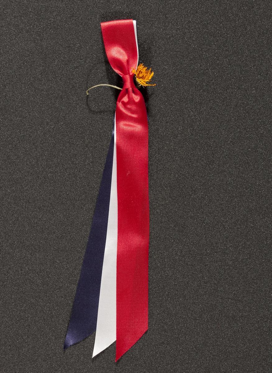 """17. mai-sløyfe innsamlet etter terrorhandlingen 22. juli 2011 fra minnesmarkeringene i Lillestrøm.   Enkel 17. mai-sløyfe med en liten ekstra pynt; en liten gul blomst som giveren har festet til sløyfens nål. Ved nålen er sløyfen føyet sammen av et rødt bånd på ca. en cm. Det er festet med røde sting. Nålen er festet i denne """"knuten"""". Sløyfen er hel og ren. Blomsten er en vanlig blomst å finne i plenen eller i en grøftekant."""