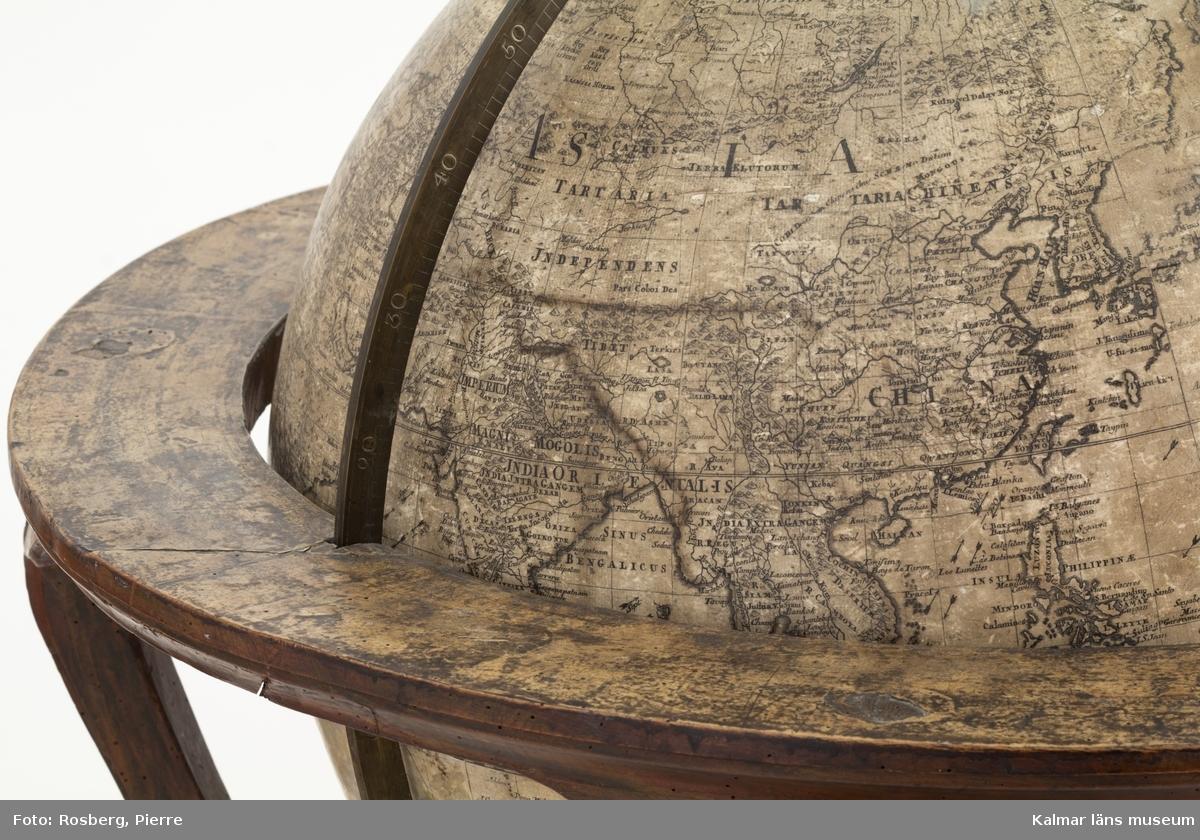 KLM 44704:1. Jordglob. Globen är monterad i en elegant rokokoställning med beslag. Meridianbågen är tillverkad av mässing. Själva globen är tillverkad av papier-maché i två klothalvor som sedan sammanfogats, därefter har globen fått ett gipsskikt som slipats. Troligen omges globaxeln av ett rör eller krysstag för att stötta konstruktionen. Man vet inte med säkerhet hur globerna ser ut inuti. Limningen av kopparsticken mot globklotet är av högsta kvalité. Glob framställd av Anders Åkerman, Uppsala, även benställningen framställd i Åkermans verkstad. Globen daterad: 1766. Hör samman med KLM 44704:2 Himmelsglob.