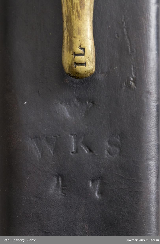 KLM 4871. Huggare med balja. Bygelfäste med hjärtformig parerplåt av mässing. Kaveln snedräfflad. Klingan krokig. På bygeln stämpel: TALFN. På parerplåtens nerböjda avslutning stämpel: IL. På läderbaljan W. K. S. - 47.  Svensk infanterihuggare.