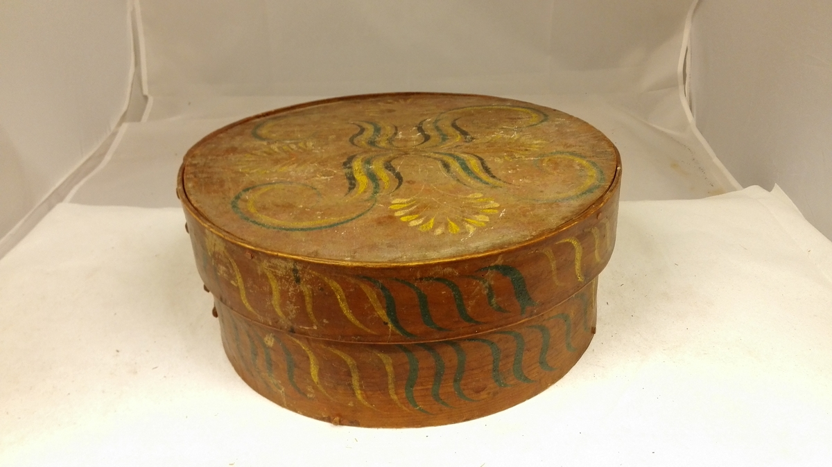 1 tine  Konehuetine som foregaaende, men mindre, diameter 32,6 cm, höide med laag 13,5 cm. Brunmalt med blaa og gule slyngninger.  Samtlige disse gjenstander (11643 - 53) Kjöpt ved Kjöbmand Th. Lindström, Lærdal.