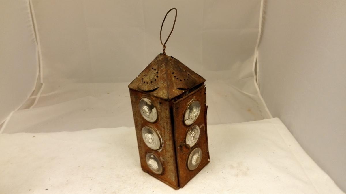 Prismeforma med pyramideforma topp.  Hengsla sidedør med jarnring som halde. 3 koniske vindauge på kvar vegg/ side. Perforerte skjold på toppen. Tvinna jarntrå d som topphalde. Innvendig holdar for lys sentrert i botn.
