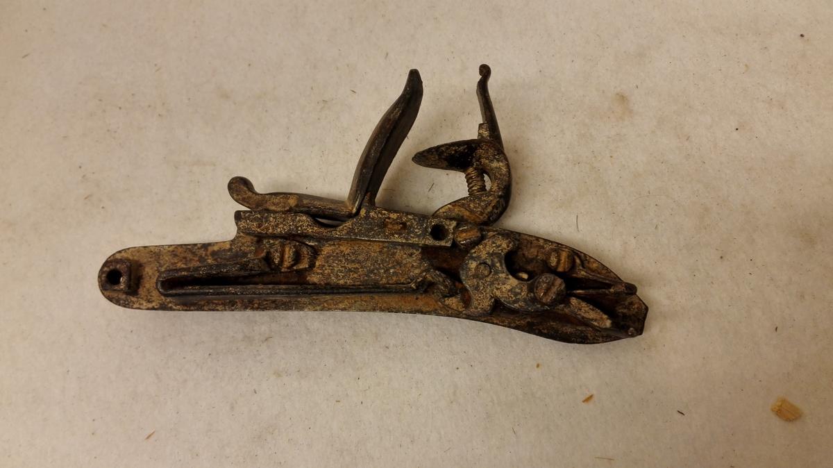 1 flintelaas fra et gevær.  Et noget defekt flintlaas fra et gevær. Gave fra Christen Offerdal, Feios.
