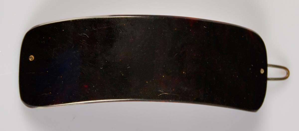 Hårspenne med noko boga form, med metall klype på baksida. Mørk brunt plastliknande materiale.