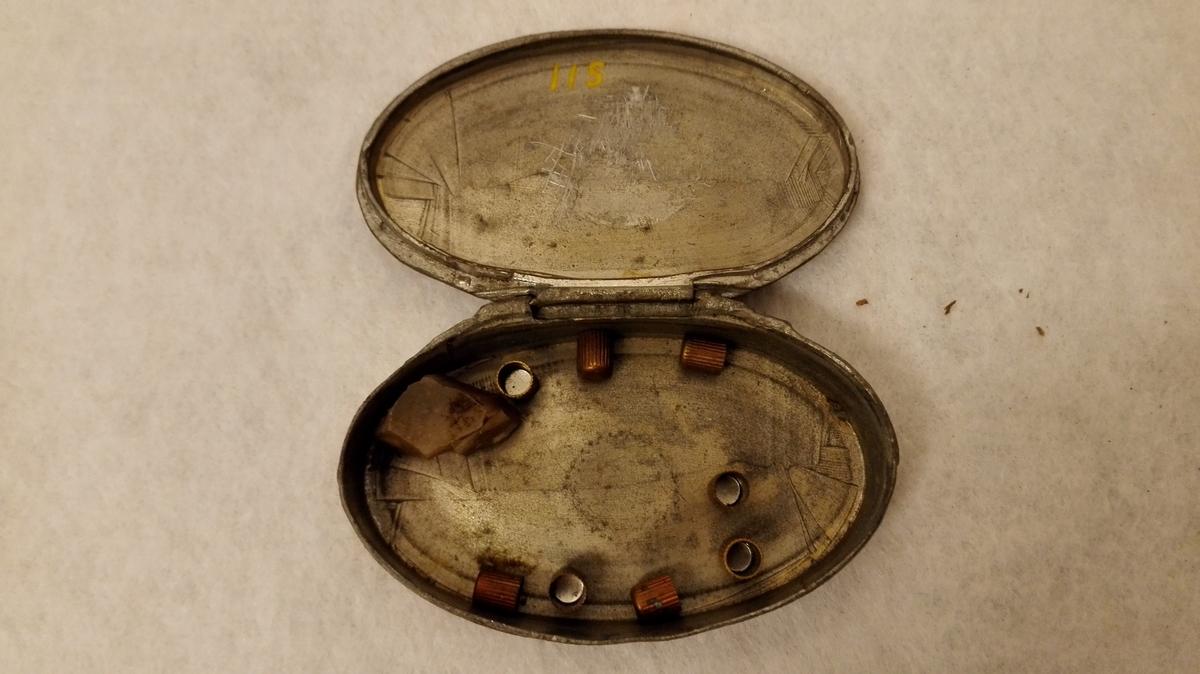 Form: Oval dåse med støypte forsiringar. H.K. Heiberg brukte dåsen til knallperler. Anne-Stina Hals: Utstillingskatalog, Kunstindustrimuseet i Oslo 1976.