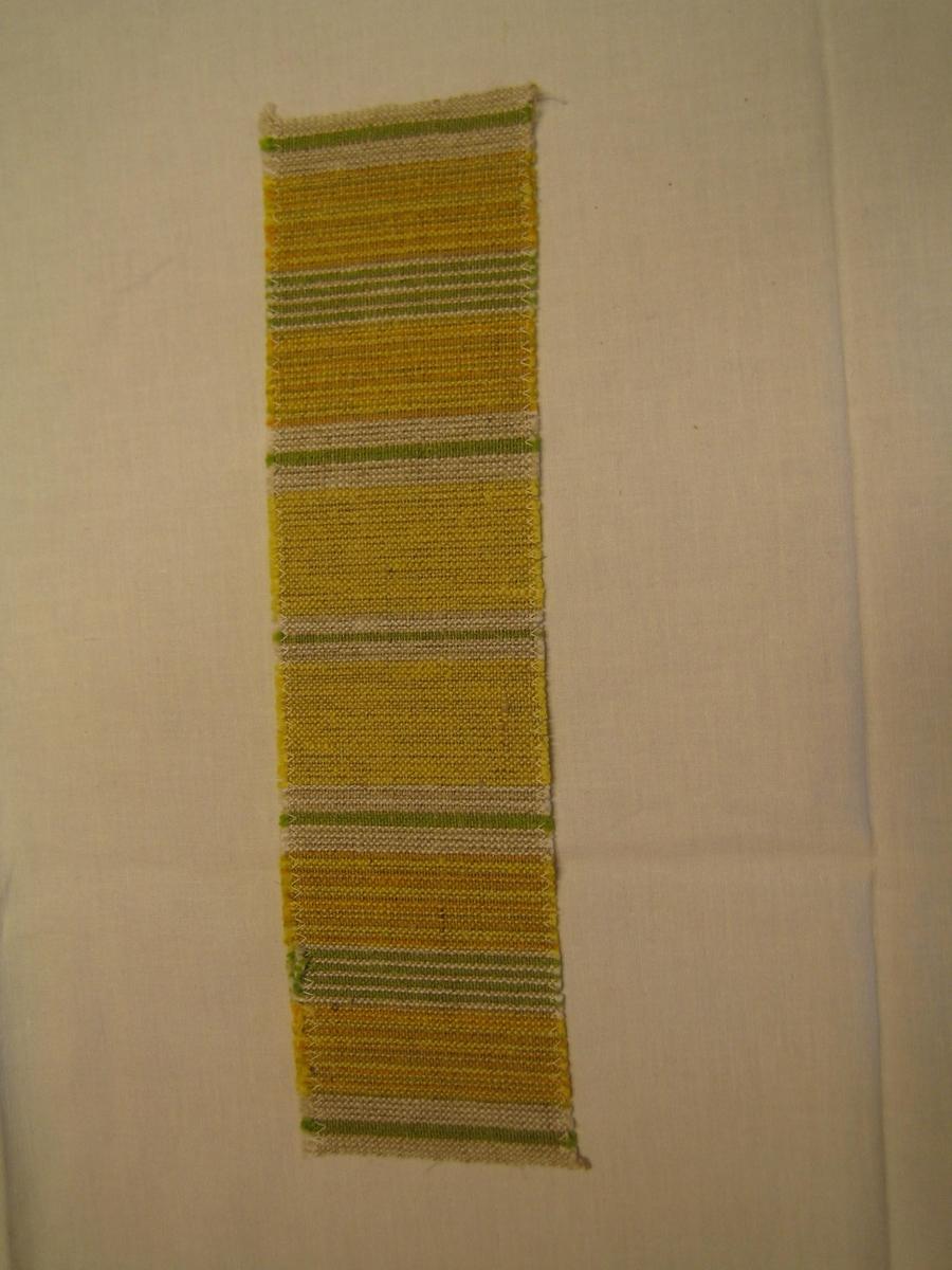 Vävprov på löpare med cottolin i gult, orange,grönt,vitt och oblekt i varpen och oblekt lin i inslag. Provet är vävt i tuskaft.