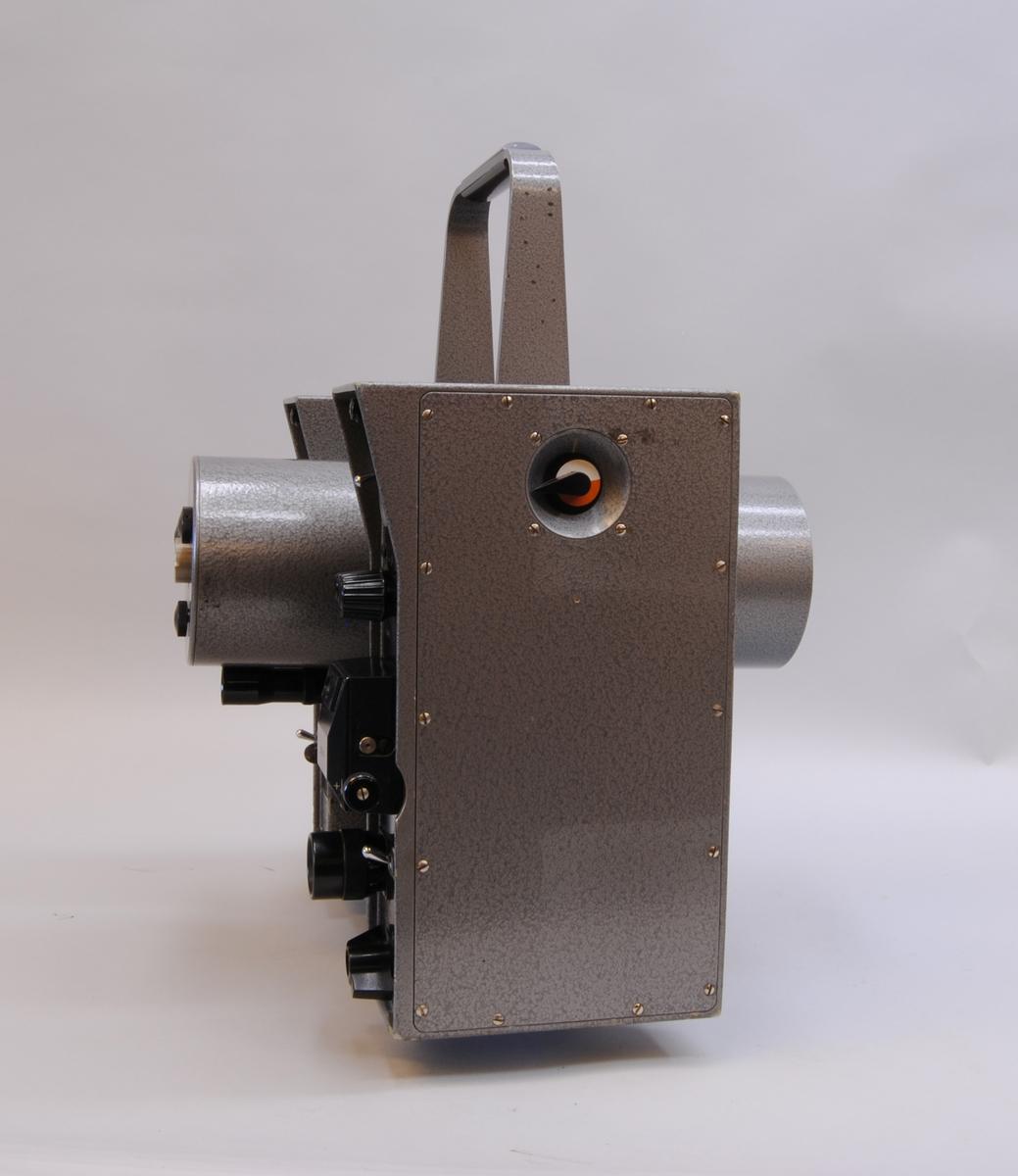 AGA Geodimeter modell 6. Mätinstrumentet har ett grått plåthölje. I mitten av instrumentet finns en cylinderformad tub som går att vinkla till horisontellt läge och skruvas åt för att fastsättas. På sidorna om tuben är två rektangulärt stående partier med olika reglage på den sidan som instrumentet manövreras från. Instrumentet står på en rund vridbar platta som är avsedd att fästas i ett stativ. Se även fodral Jvm23132:2-3 samt tillbehör Jvm23132:4-9.