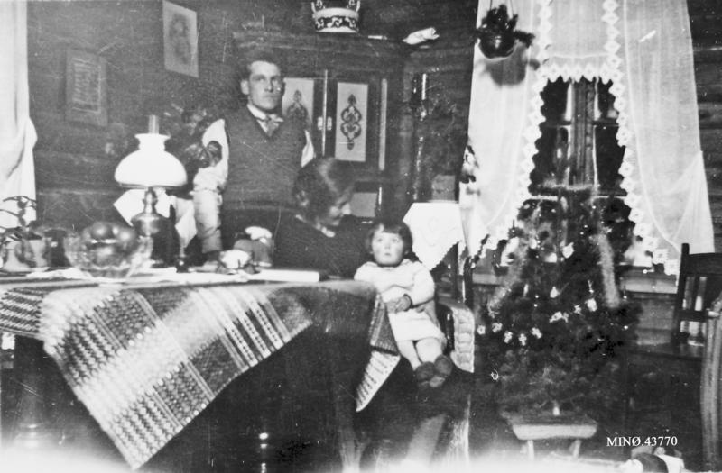 F. v. : Esten Flyen, Signe Flyen med Inger (Flyen) Nytrøen på fanget. Møbler snekret av Esten Flyen som gikk på snekkerskole. Bordduken er vevd av Signe Flyen, ho hadde gått vevkurs. Grøtdall er laget av Lars Flyen. Bildet er tatt i stua på Husøy. Familien flyttet inn i 1933. Bureisingsbruk. Bildet tatt i 1935.